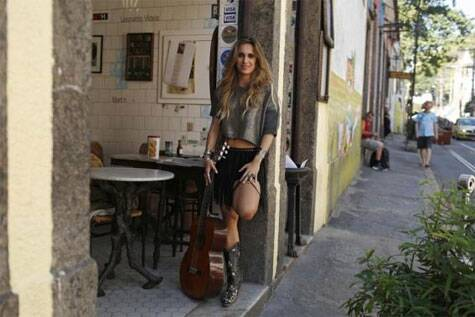 Brazilian singer Dora Vergueiro poses at the entrance of the Bar do Mineiro in Santa Teresa neighborhood in Rio de Janeiro June 5, 2014.  Source: Reuters
