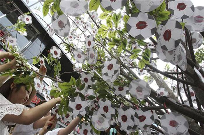 Women hang paper footballs on a tree during an event in Seoul, South Korea,  wishing the South Korean national football team to perform well at the World Cup in Brazil. (Source: AP)