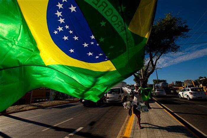 A street vendor sells representations of Brazil's national flags near the Arena Castelao in Fortaleza, Brazil ahead of the opening match between Brazil and Croatia on Thursday. (Source: AP)