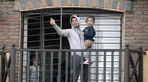 Luis Suarez waves to fans from his home's balcony, alongside his children in Montevideo. Suarez returned to Montevideo early Friday, arriving too late to see the hundreds of Uruguay fans who had gathered the previous night to give him a hero's welcome despite his World Cup banishment. (Source: AP)