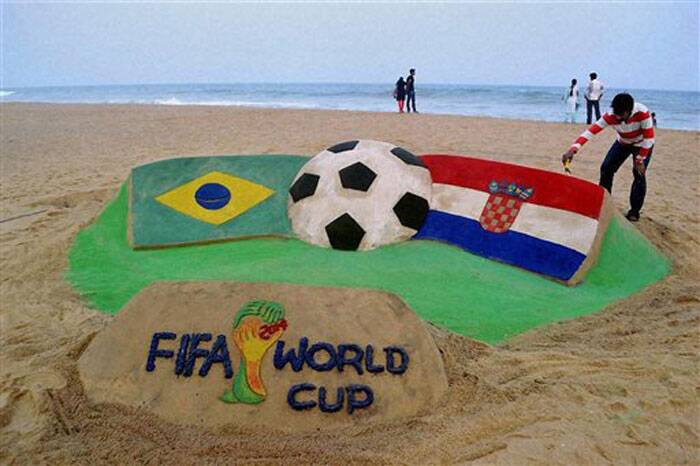 Renowned Indian sand artist Sudarsan Pattnaik creates a sand sculpture of the national flags of Brazil and Croatia to mark the opening match of FIFA World Cup 2014  at Puri beach on Wednesday. (Source: PTI)