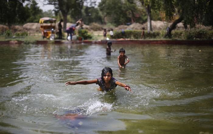 Children swim in a pond on a hot summer afternoon in New Delhi. <br /> Heat wave conditions prevailed in the capital with mercury crossing 46.7 degrees Celsius (116 degrees Fahrenheit). (Source: AP)