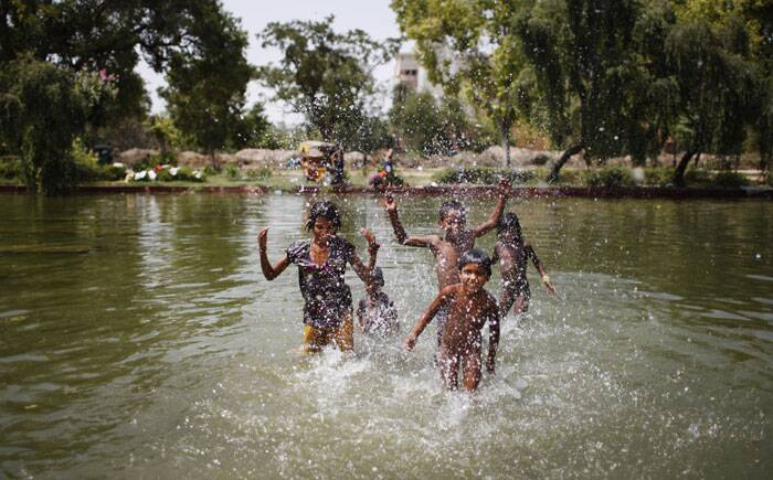 Children are seen playing in water on a hot summer afternoon in New Delhi. (Source: AP)
