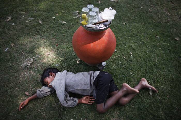 A boy, selling lemon water in an earthen pot, sleeps on the grass at a public park on a hot summer afternoon in New Delhi. (Source: AP)