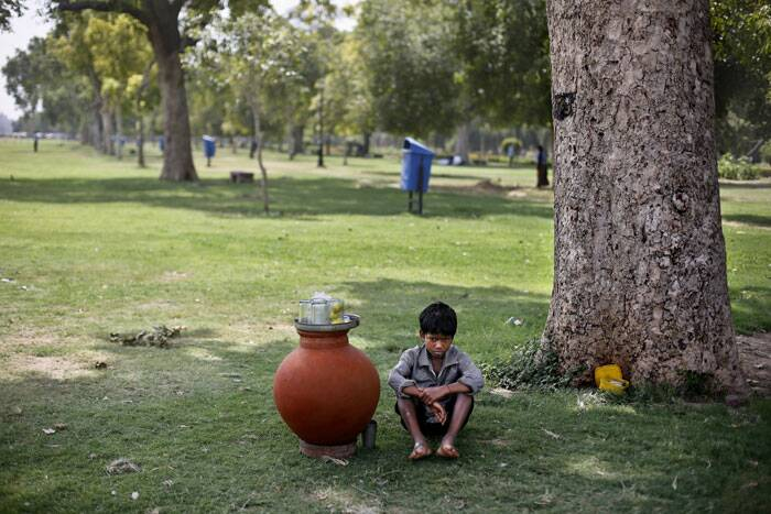 A boy, selling lemon water, waits for customers inside a public park on a hot summer afternoon in New Delhi. (Source: AP)