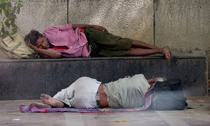 Two men take nap in a shade alongside a road on a hot day in New Delhi on Friday. (Source: PTI)