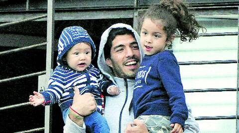 Suarez at home with his children. The Uruguayan told FIFA's disciplinary panel that he did not deliberately bite Chiellini at the World Cup. (Source: AP)