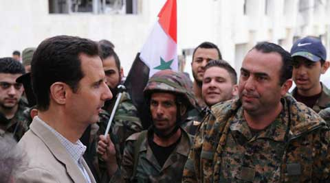 Syrian President Bashar Assad, left, talks to government soldiers during his visit to the Christian village of Maaloula, near Damascus, Syria. (AP)