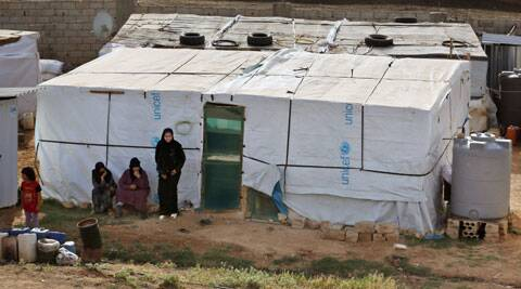 In this Thursday, June 19, 2014 photo, Syrian refugee women stand outside their tent at a Syrian refugee camp in the eastern Lebanese town of Majdal Anjar, Lebanon. (Source: AP)