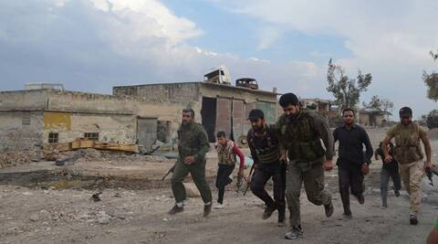 This photo provided by the anti-government activist group Aleppo Media Center (AMC), which has been authenticated based on its contents and other AP reporting, shows Free Syrian Army fighters running at one of the front lines in the town of Sheikh Najjar, in Aleppo, Syria. (AP)