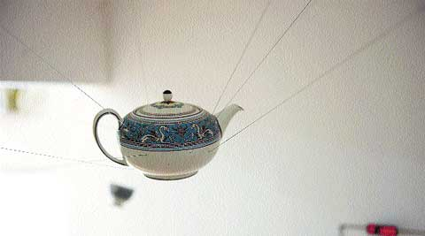 An heirloom porcelain teapot is suspended by magnets. (Source: Express Photo)