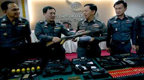 Thai police officers examine war weapons they seized from a raid early this month being displayed at a news conference in Bangkok, Thailand. (Source: AP)