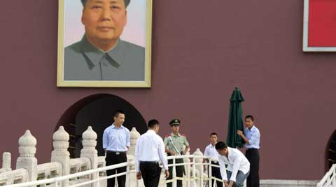 A Chinese plainclothes security person pulls a concrete block near a portrait of late Chinese leader Mao Zedong on Tiananmen Gate in Beijing. (AP)