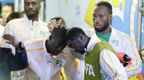 The Toure brothers greet each other before Ivory Coast's World Cup game against Japan. Their younger brother Ibrahim Toure died on Thursday. (Source: AP)