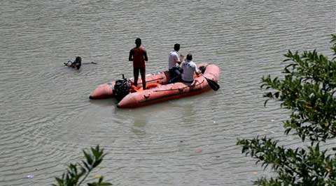 Indian rescuers search the Beas River after dozens of students were swept away when a dam released a rush of water without warning at Pandoh. (Photo: AP)