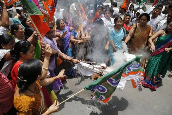 BJP workers raise slogans and burn an effigy of Akhilesh Yadav, chief minister of Uttar Pradesh, during a protest against the gang rape of two teenage girls, in Allahabad. (Source: AP)
