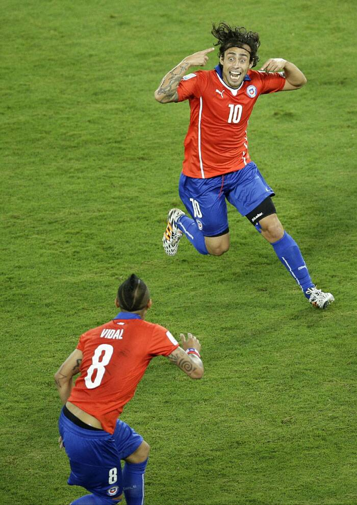 Chile's Jorge Valdiva celebrates by twirling his fingers around his temples with teammate Arturo Vidal after scoring against Australia. (Source: AP)