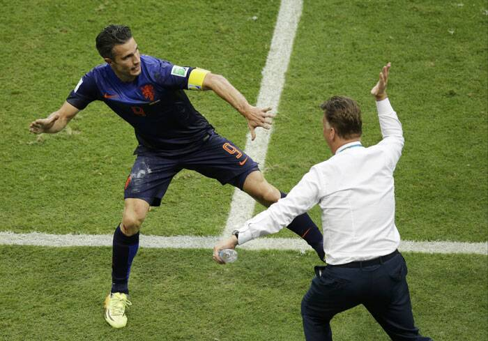 "Robin van Persie high fives coach Louis van Gaal after scoring via a acrobatic header that earned him the title ""The flying Dutchman"". (Source: AP)"