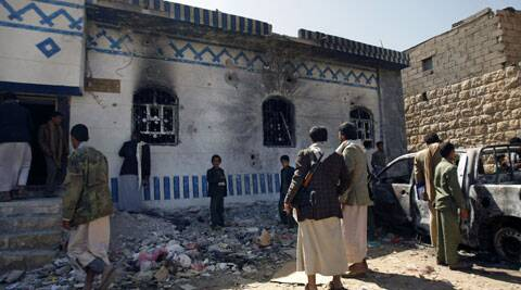 Yemenis look at a building damaged during a police raid on a hideout of al-Qaida militants in Arhab region, north of Sanaa, Yemen. (Source: AP)