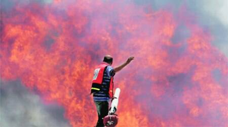 Palestinian firefighters try to extinguish a cargo terminal fire at Karni crossing between Israel and  Gaza after it was shelled by Israeli tanks, according to terminal's employees, Saturday. (Source: AP)