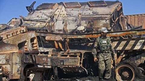 An Afghan policeman stands near a destroyed NATO supply truck in Behsud district of Jalalabad east of Kabul, Afghanistan. (Source: AP)