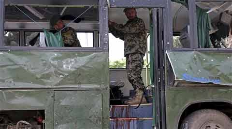 Afghan National Army (ANA) soldiers prepare to remove a destroyed military bus at the site of a suicide attack in Kabul, Afghanistan. (Source: AP)