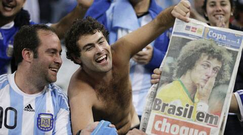 An Argentine fans holds a newspaper showing a dejected David Luiz after Brazil's 7-1 loss to Germany in the semi-finals. (Source: AP)