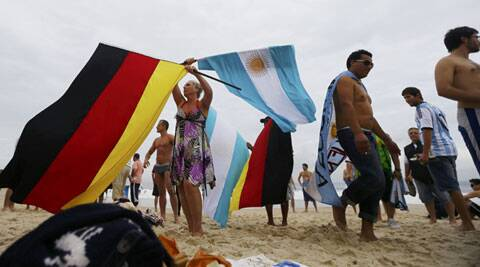 A woman waves German and Argentine flags on Copacabana beach.  The winner between Germany and Argentina in the final will get  million in prize money. (Source: Reuters)