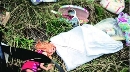 A doll and other personal effects lie on the ground at the crash site near Hrabove Saturday. 	(Source: AP)