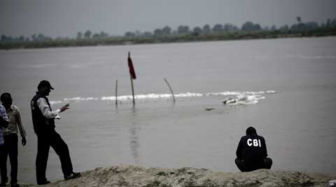 The bodies of the minor victims could not be exhumed as overflowing Ganga flooded their graves (marked by red flag) in Badaun. (PRAVEEN KHANNA)