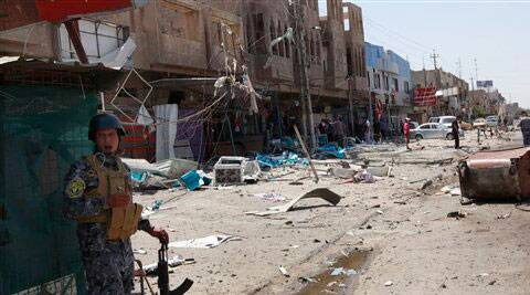 An Iraqi policeman and civilians inspect the site of a bomb attack in the Jihad district in Baghdad. ( Source: AP )