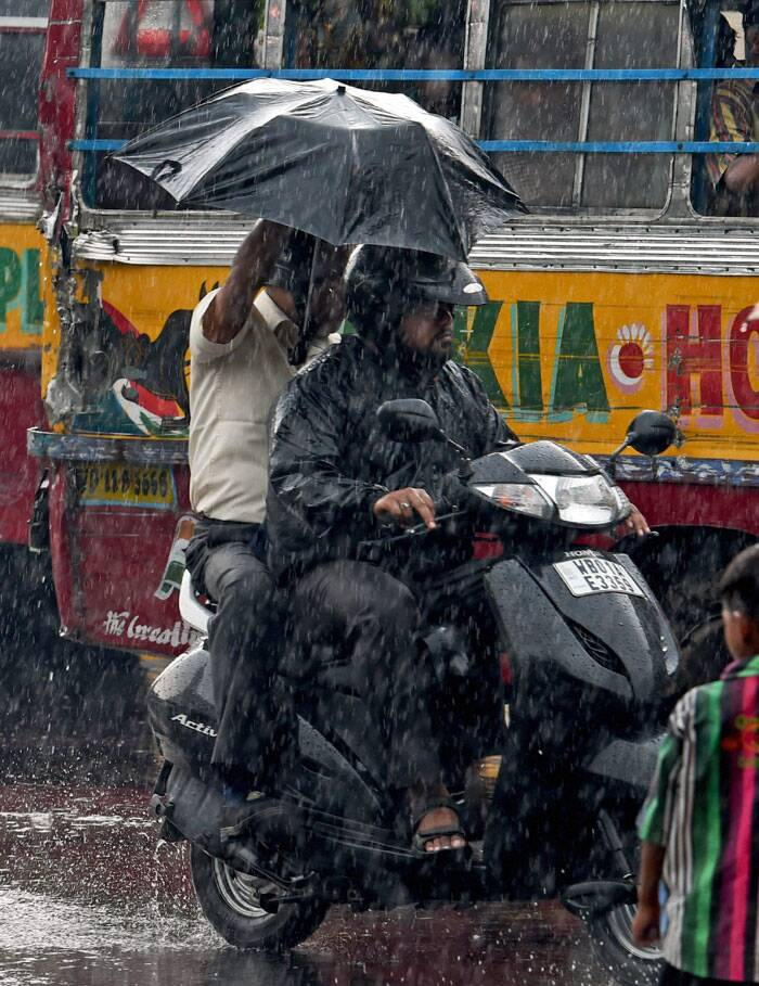 Scooter riders use an umbrella as it  rains heavily in Kolkata on Thursday. (Source: PTI)