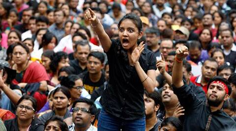An angry protester points her finger towards the Bangalore police chief during a protest against alleged police inaction after a six-year-old was raped at a school, in Bangalore. (Source: PTI)