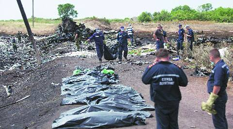 Ukrainian workers carry a victim's body in a bag as pro-Russian fighters stand guard at the crash site. (Source: AP)