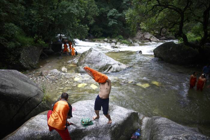 A devotee removes his t-shirt before taking a dip in the Bagmati River.<br /> The faithful, chanting the name of Lord Shiva, run about 15 km  barefooted toward Pashupatinath temple seeking good health, wealth and happiness. (Source: Reuters)