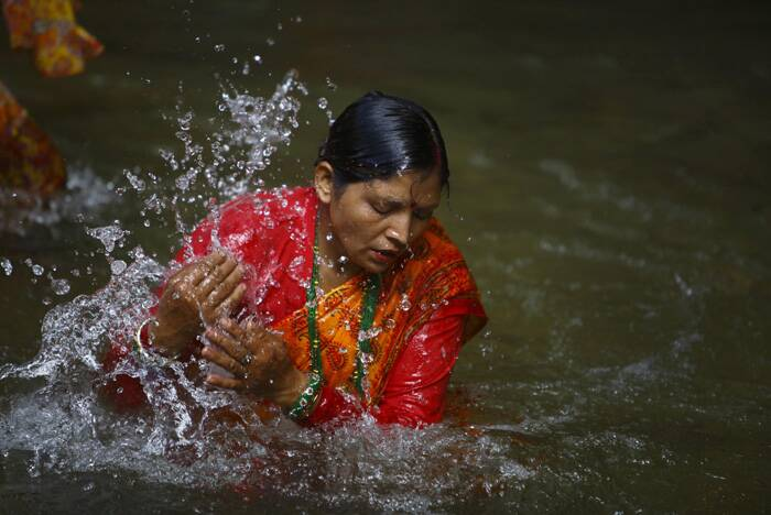 A devotee takes a dip at the Bagmati River as she participates in the 'Bol Bom' pilgrimage. (Source: Reuters)