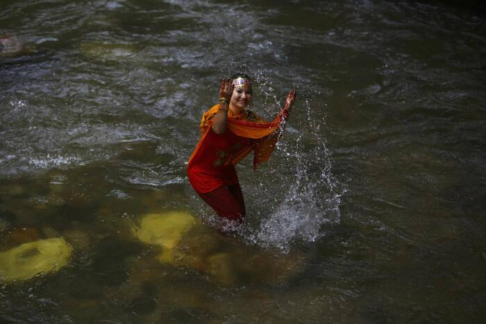 A devotee plays with water during the  pilgrimage. (Source: Reuters)