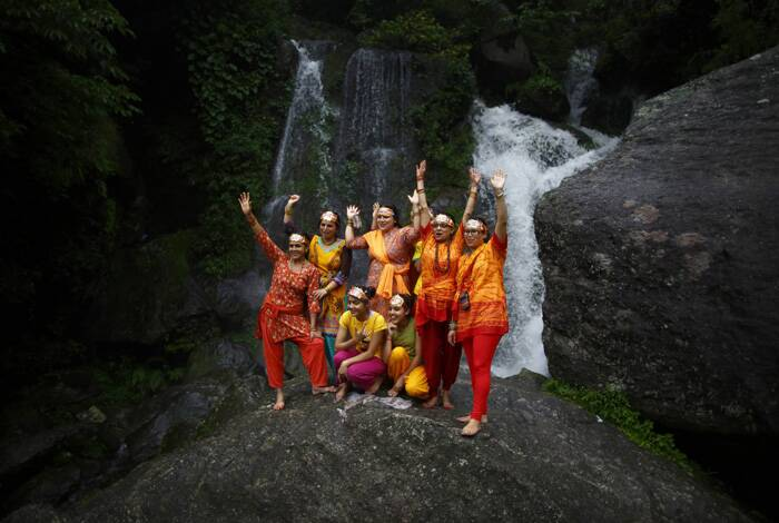 Devotees pose for pictures  in front of the waterfall during the 'Bol Bom' (Say Shiva) pilgrimage in Kathmandu. (Source: Reuters)