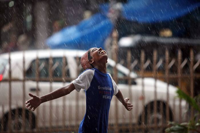 A boy stretches his arms and looks skyward as rain falls in Hyderabad. (Source: PTI)