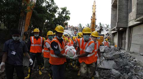 Rescuers, carry a worker's body they pulled out from the rubble of a building that collapsed late Saturday during monsoon rains. (Source: AP)