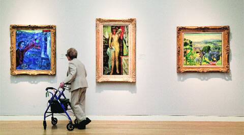 A woman browses impressionistic paintings during a preview exhibition for Sotheby's Spring Evening Sale in New York. (AP)
