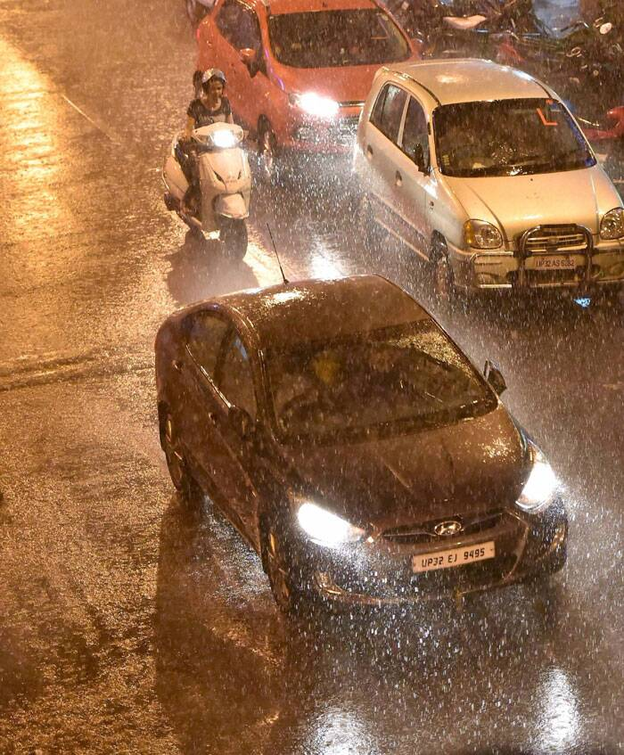 Vehicles move at a road in heavy rains in Lucknow. (Source: PTI)