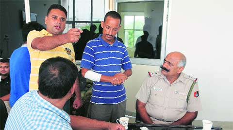 Workers of the wine shop narrate the incident to officers on Saturday. (Jasbir Malhi)