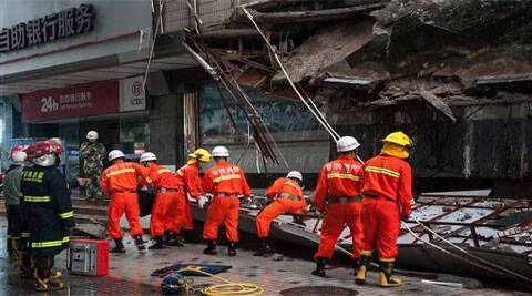 Rescuers try to remove a steal frame from a collapsed concrete roof . (Source: AP)