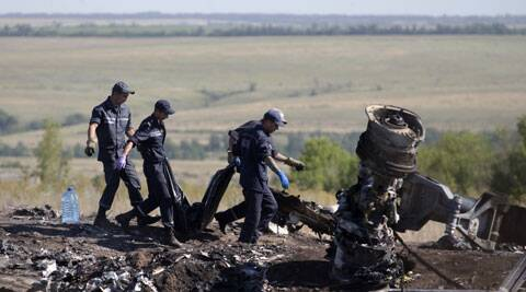 Ukrainian Emergency workers carry a victim's body in a plastic bag at the crash site of Malaysia Airlines Flight 17 near the village of Hrabove, Donetsk region, eastern Ukraine. (Source: AP)