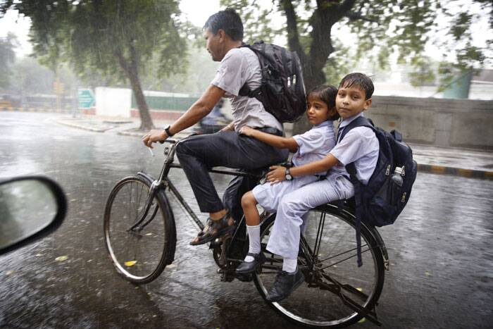 A man rides a bicycle with two children returning from school as it rains in New Delhi. (Source: AP)