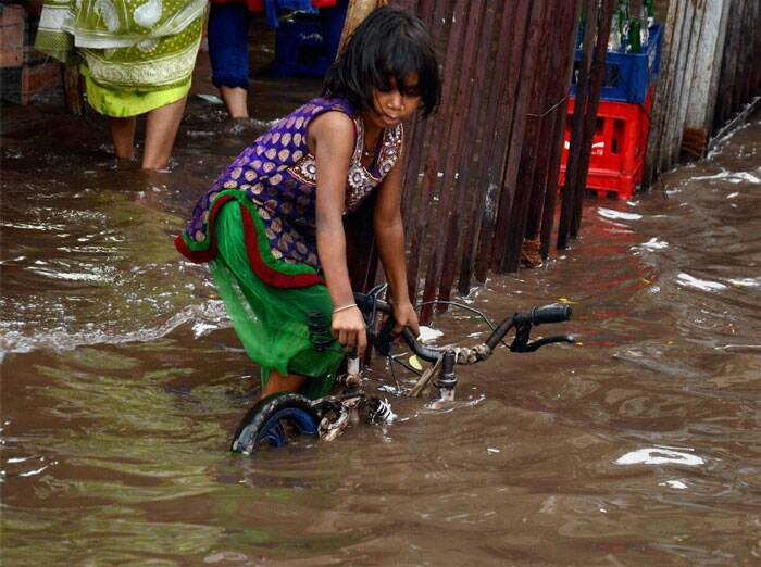 A girl trying to pull her bicycle from a waterlogged road after heavy rains in Kolkata on Thursday. (Source: PTI)