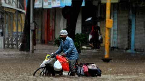 A Dabbawala wades through a waterlogged street after heavy rains in Mumbai. (Source: PTI)