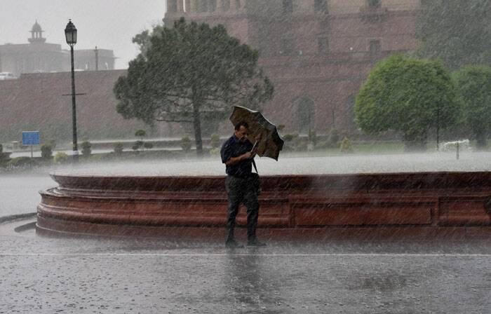 A man walks with an umbrella amid heavy shower in New Delhi on Wednesday. (Source: PTI)