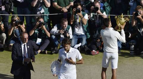 Novak Djokovic of Serbia, right, poses with the trophy for photographers after defeating Roger Federer of Switzerland, center, in the Wimbledon final (Source: AP)